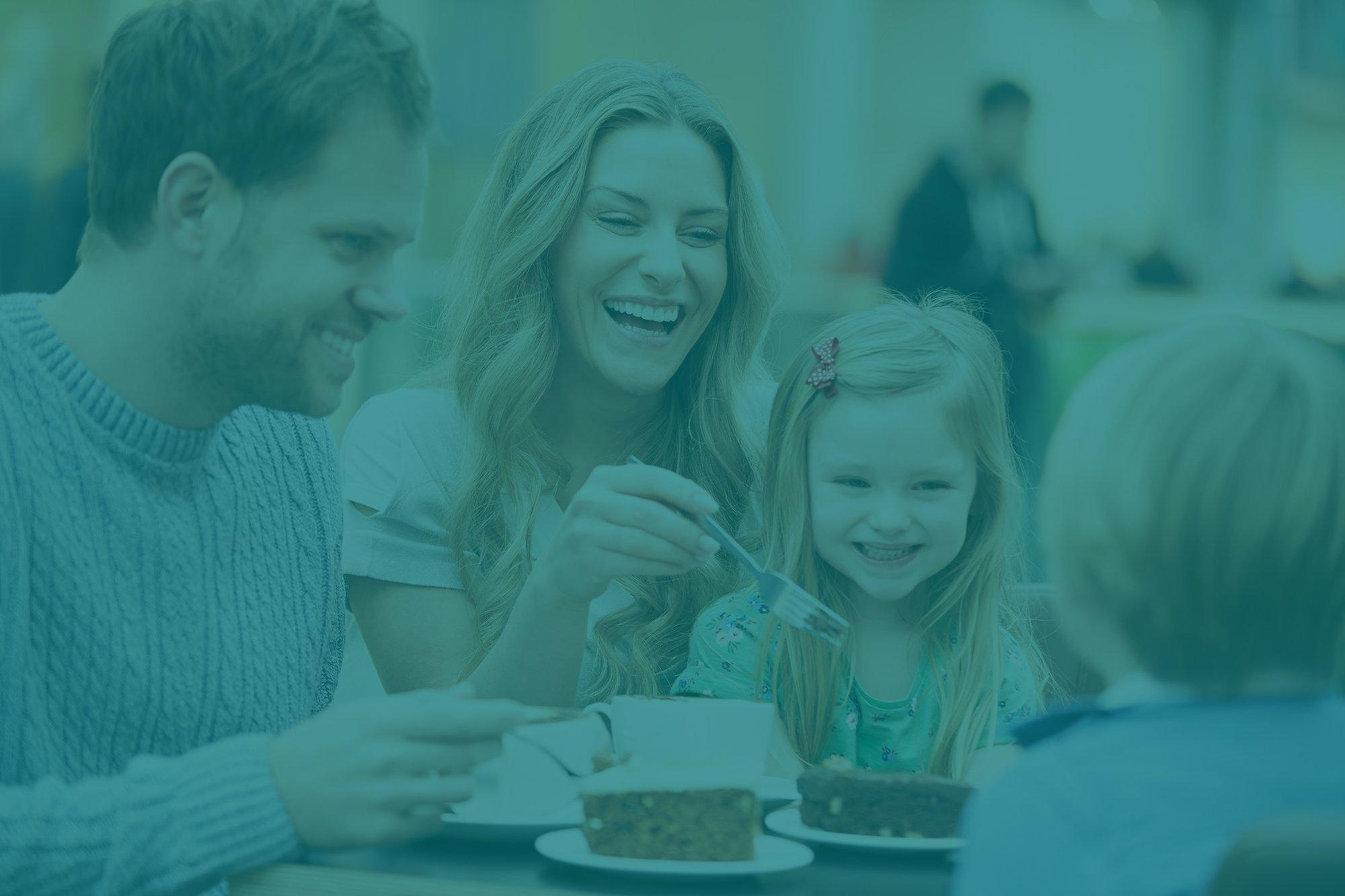Family laughing over dessert - Parkcrest Dental Group.