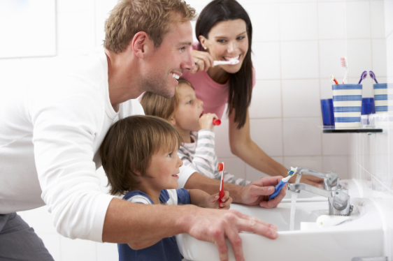 Family with kids brushing teeth - Parkcrest Dental Group.