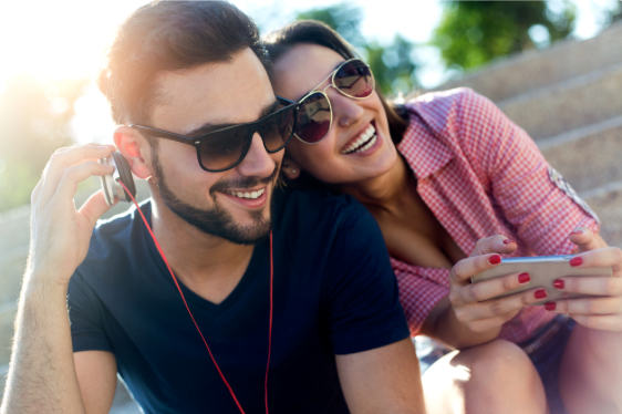 Young couple listing to music with smartphone - Parkcrest Dental Group.