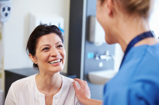 Smiling woman talking to dental professional - cosmetic dentistry.