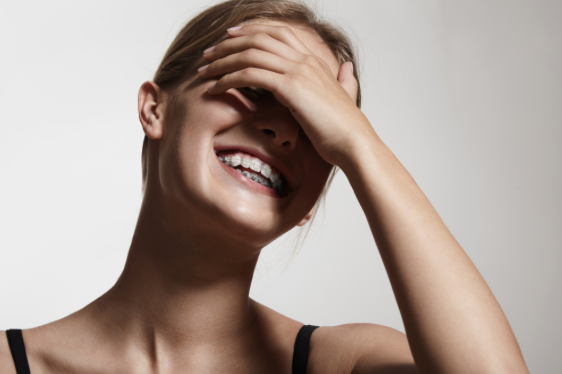 Laughing woman with braces - orthodontics.