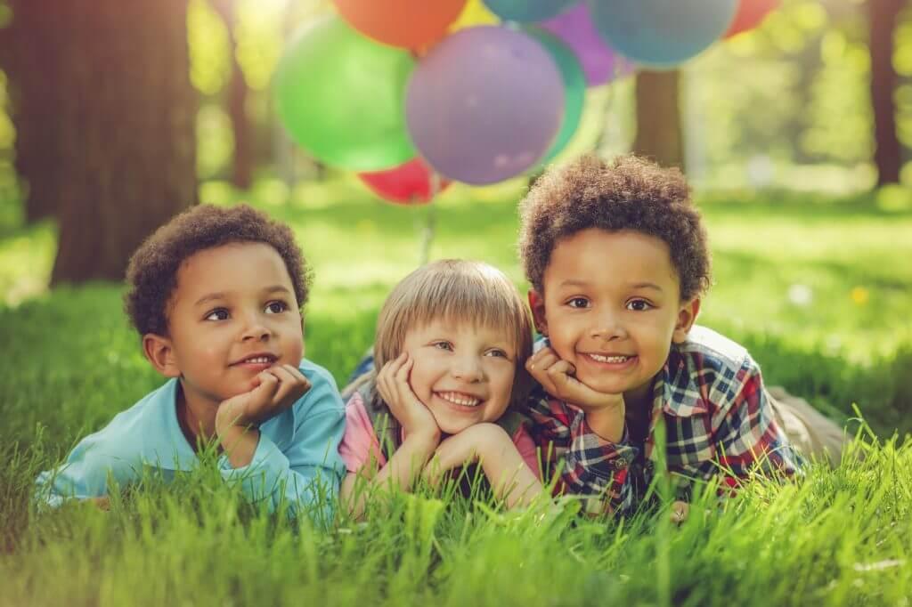 Pediatric dentistry banner image - smiling kids in garden