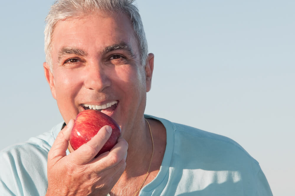 Older man eating an apple - Parkcrest Dental Group Dental Implants
