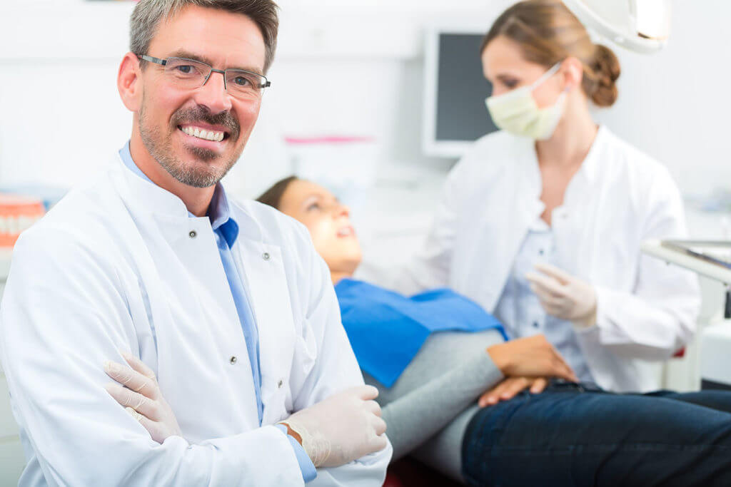 Male Oral Surgeon about to perform wisdom teeth removal procedure on a female