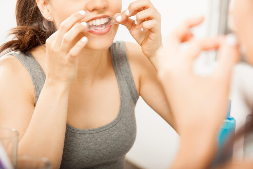 Young brunette female using a teeth whitening strip in the bathroom