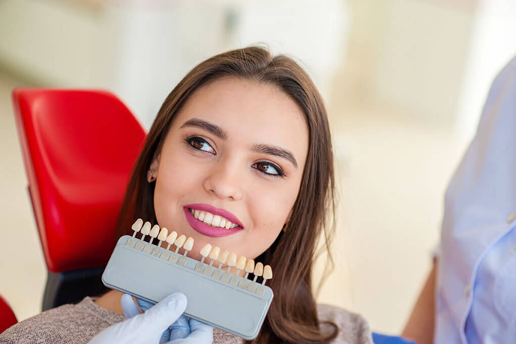 Young female selecting tooth color for dental implants