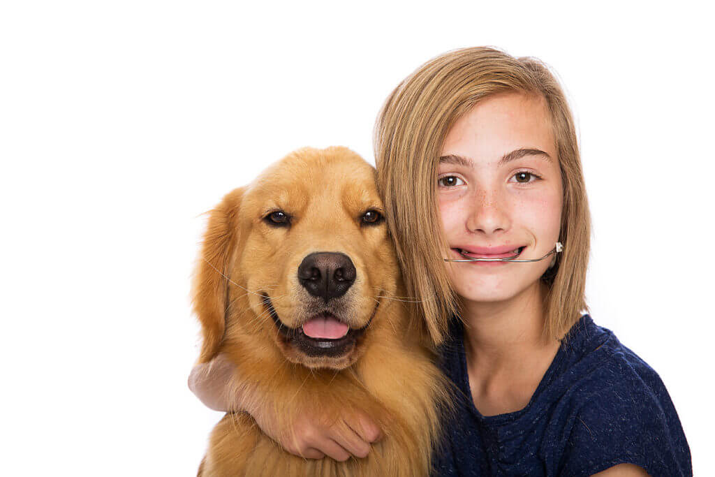 Young girl who has received orthodontic dentistry with a dog
