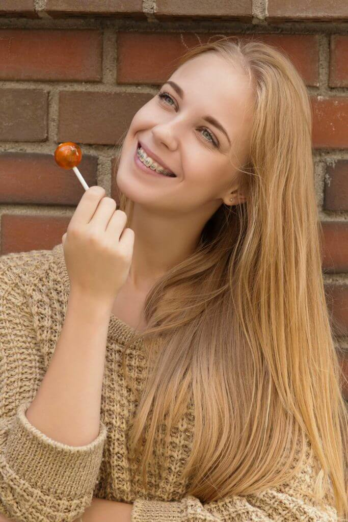 Young woman eating candy after getting braces from Dr. Steven Harrison