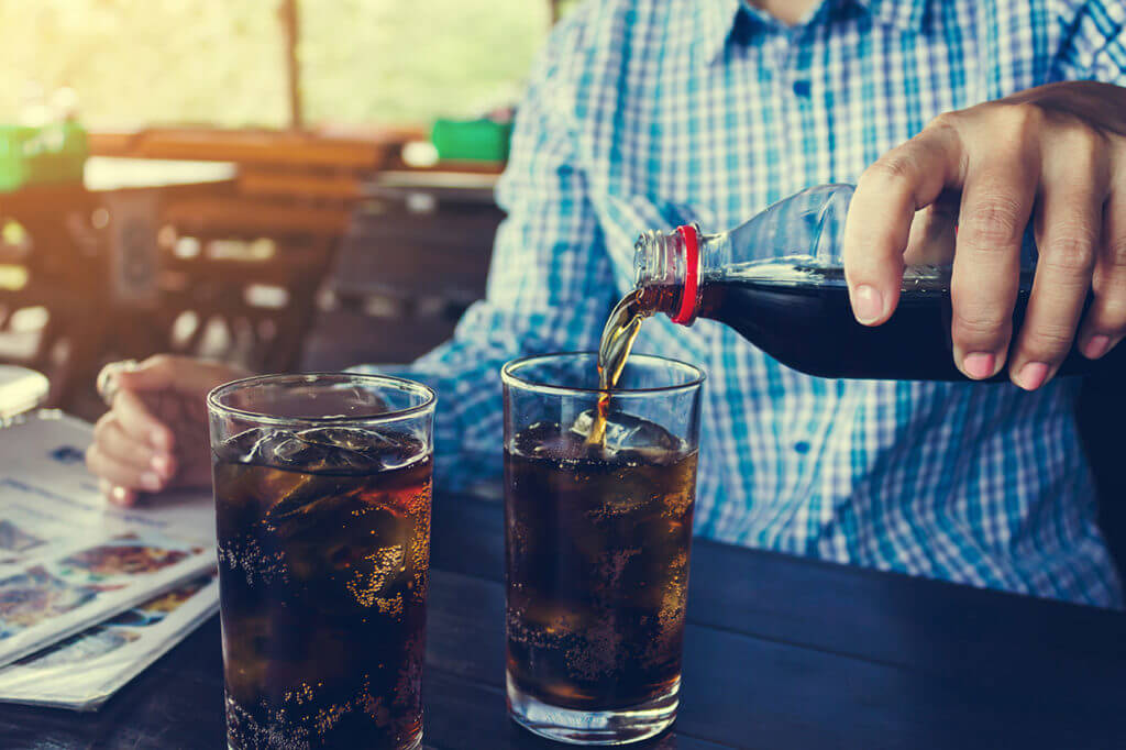 Man pouring a soda, despite advice from Dr. Harrison