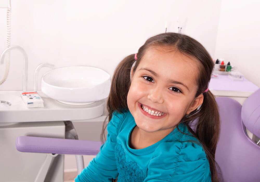 Happy child receiving pediatric dentistry work.