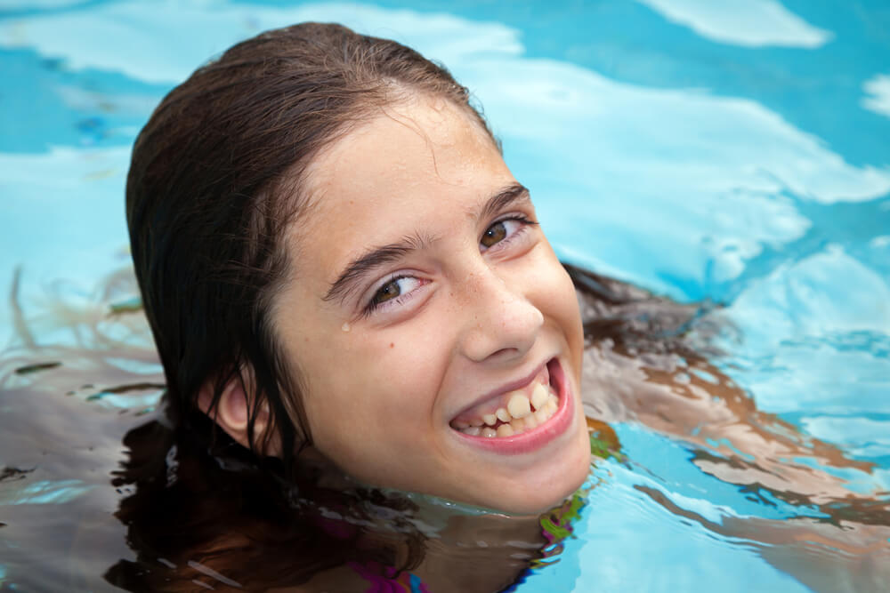 young girl swimming in pool needs orthodontics work