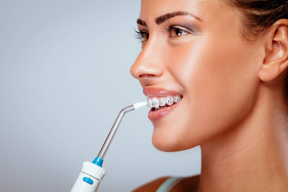 smiling young woman cleaning braces with an oral irrigator