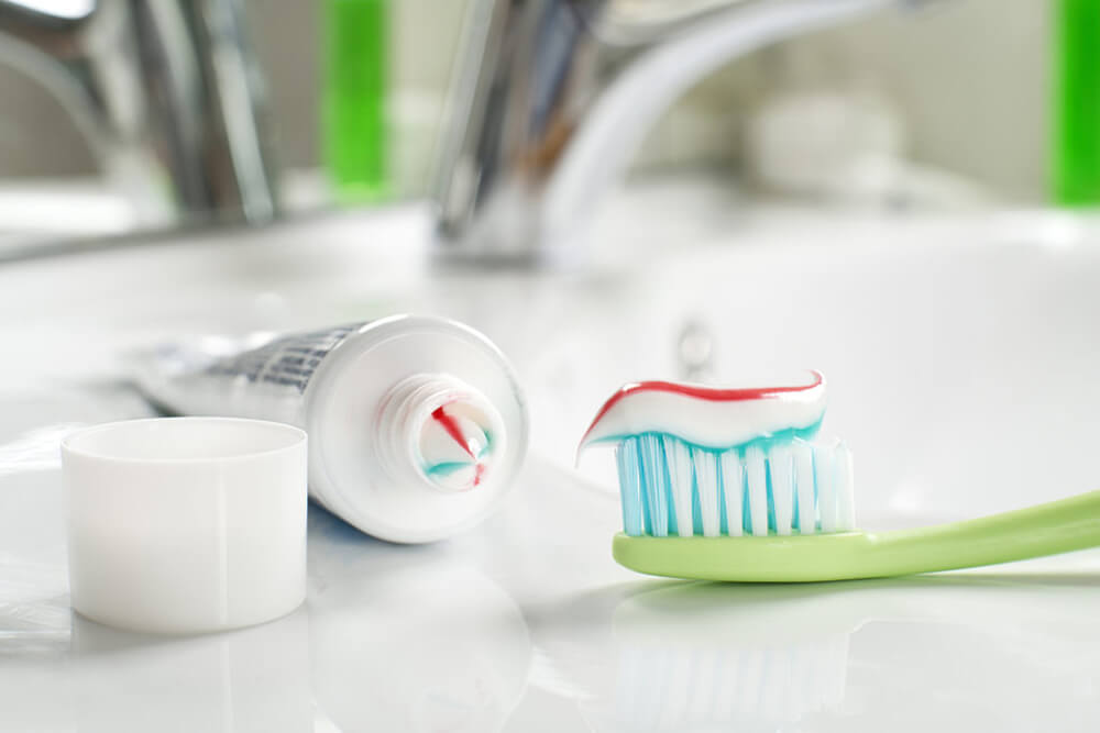 Toothpaste and toothbrush on bathroom counter