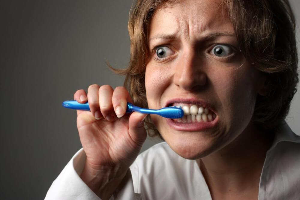 Woman brushing her teeth too hard.