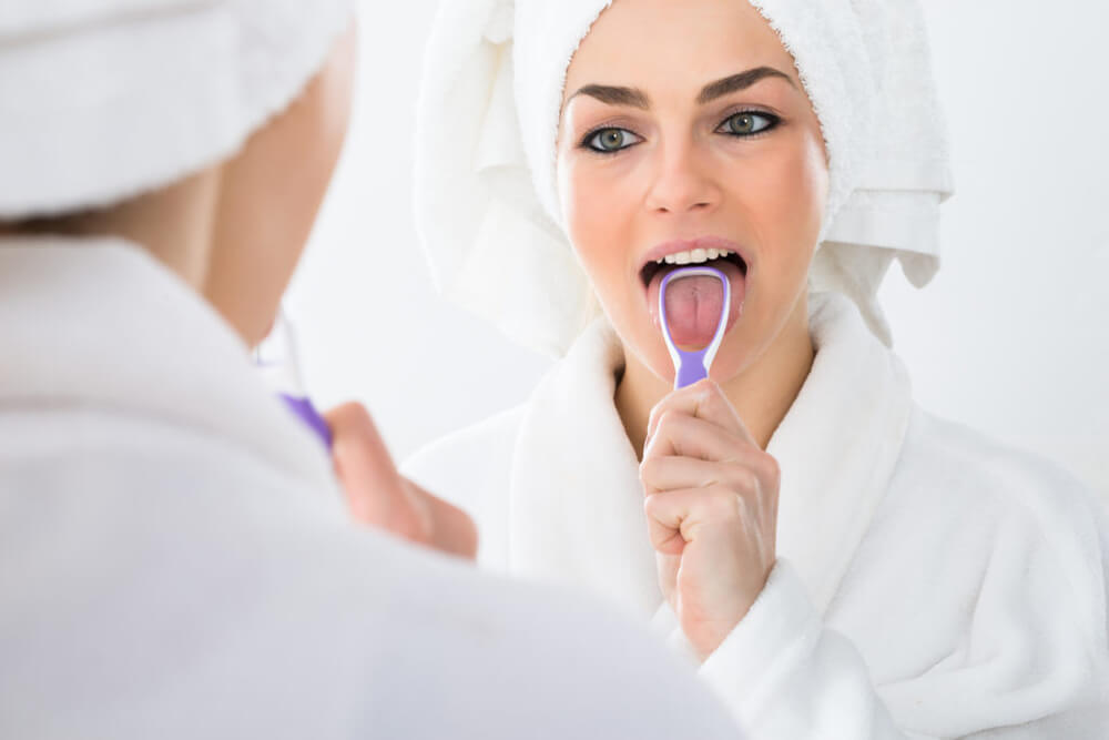 Woman looking in mirror using a tongue scraper