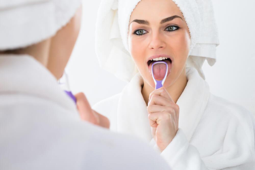 Woman looking in mirror using a tongue scraper