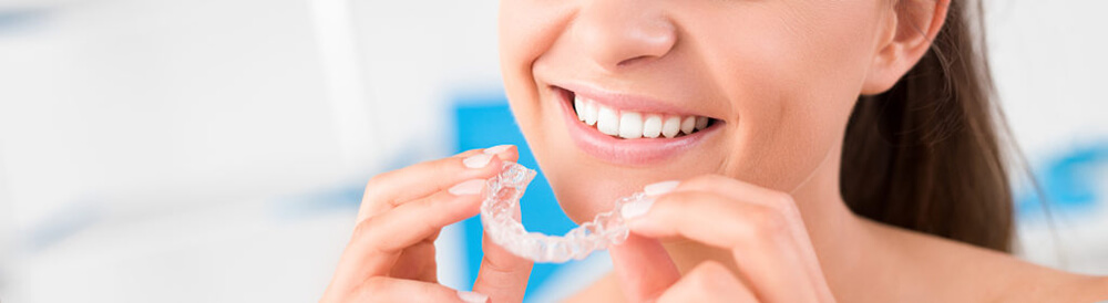 Woman-putting-on-her-Invisalign-retainer.jpg