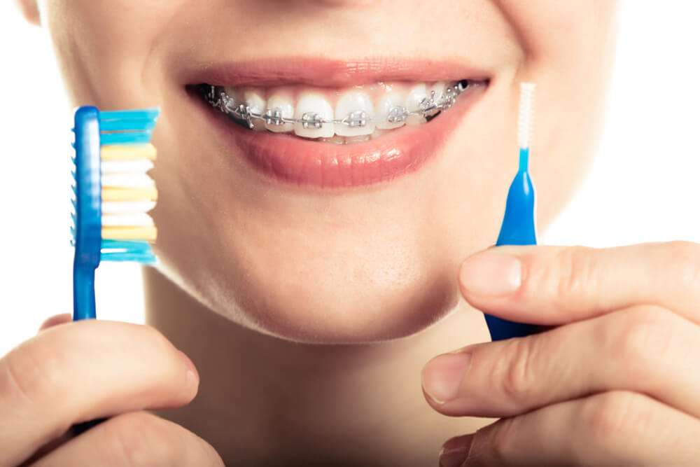 Young woman with braces holding her toothbrushes