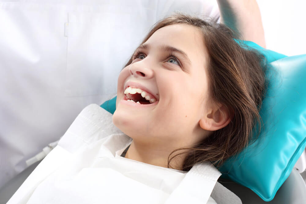 Smiling-child-sitting-in-dental-chair-looking-up-at-dentist-.jpg