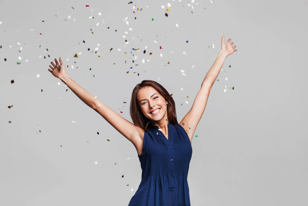A woman smiles with New Year confetti falling behind her.