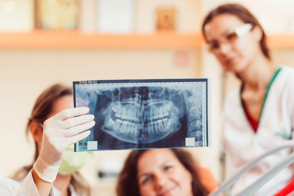 Dental professionals examine a patient's X-ray.