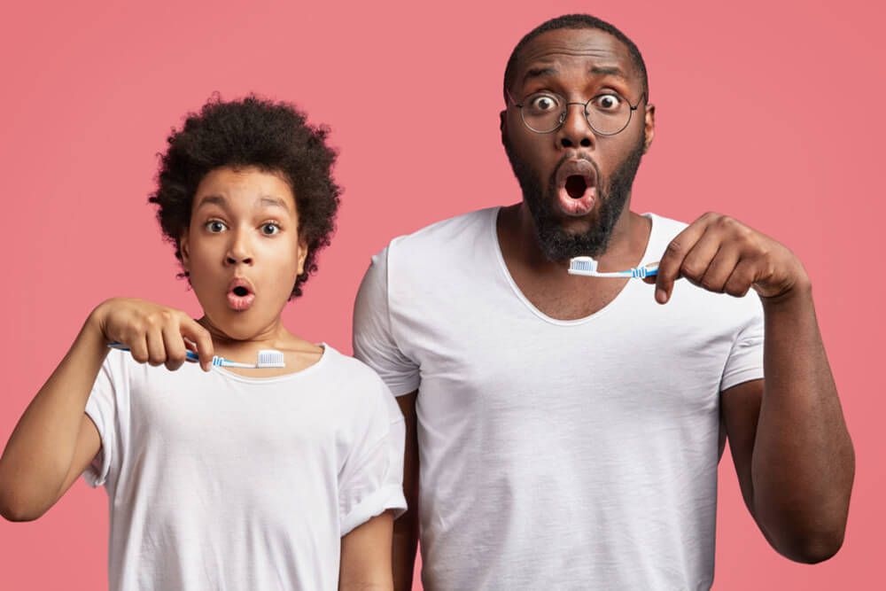 Father and son shocked holding toothbrushes