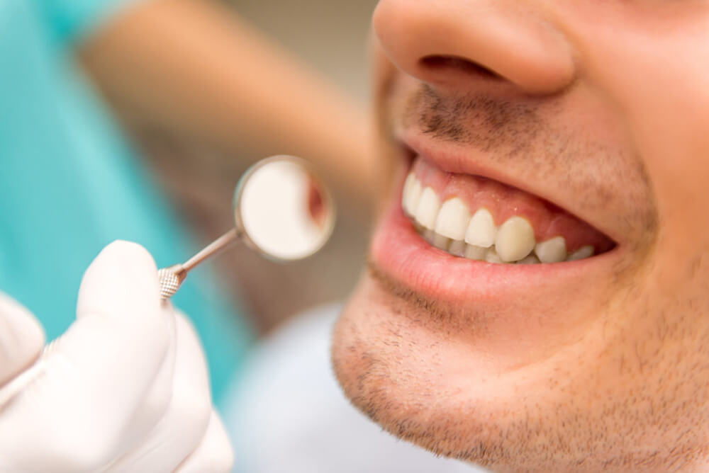 Man with beautiful white teeth getting cleaned
