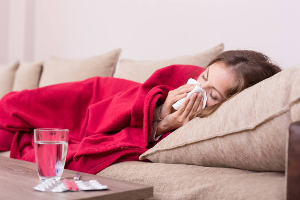 Woman with the flu on a couch.