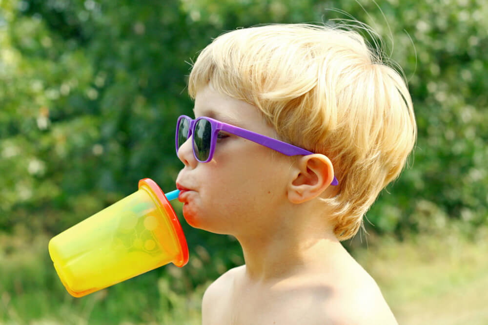 Young boy drinking juice from a sippy cup