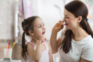 mother teaching kid daughter teeth brushing in bathroom