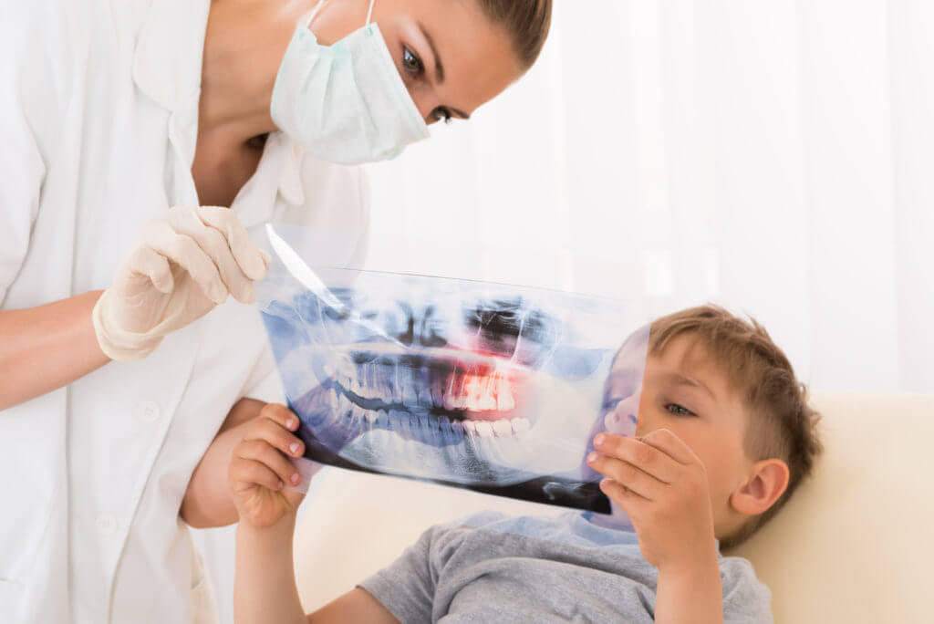 A dentist explains what is occurring with a child's teeth according to an X-Ray.ing to an X-Ray.