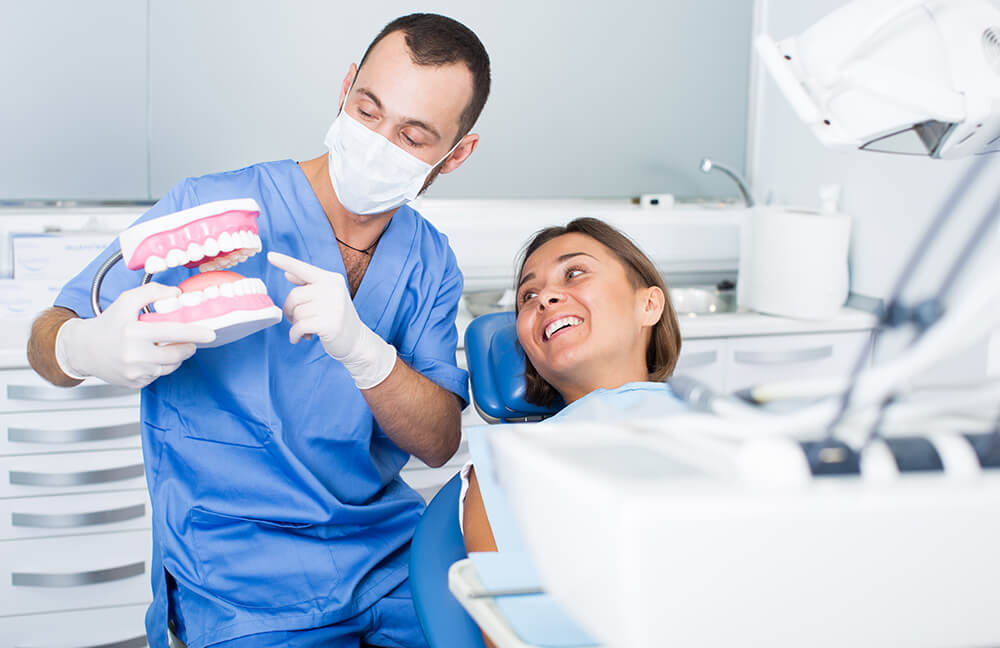 Orthodontist explaining dental hygiene to a patient