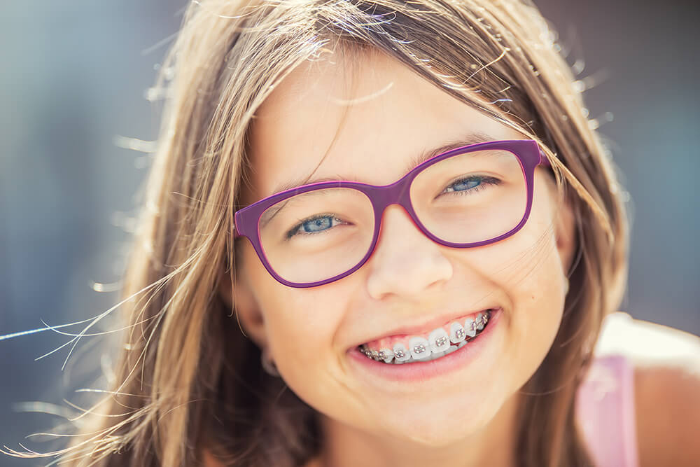 Young girl with braces smiling at the camera