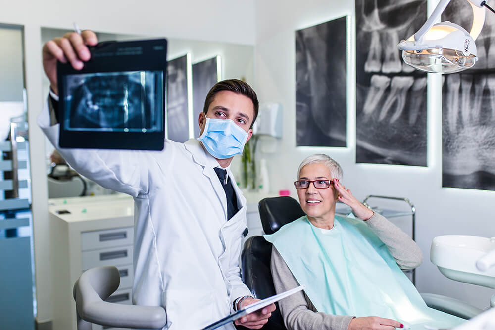 Dentist show woman an x-ray image of her teeth during a consultation