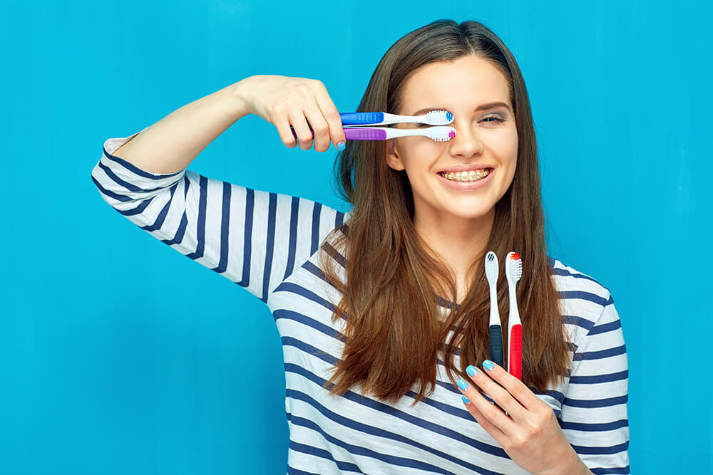 Girl holding multiple toothbrushes on a blue background