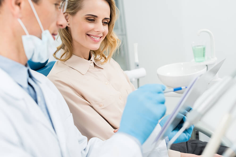 Image of a smiling woman having a cosmetic dental consultation