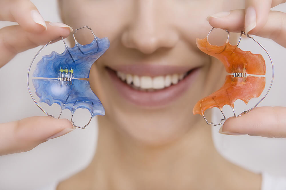 Woman holding two different retainers