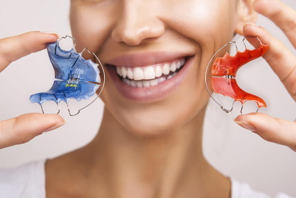 A smiling woman holds two retainers.