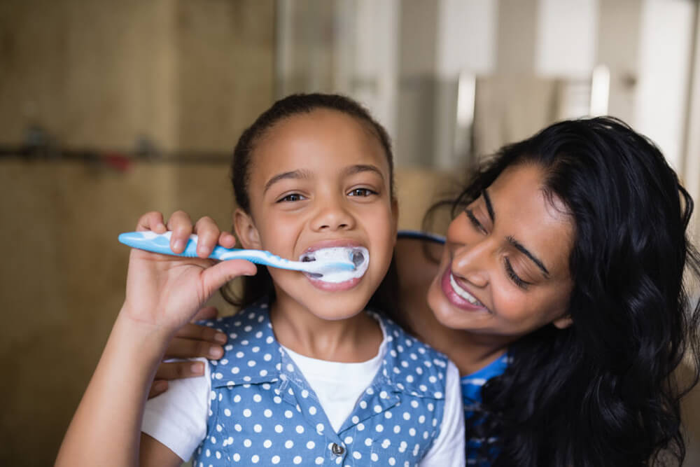 Parkcrest Dental Group Helps Someone with Brushing