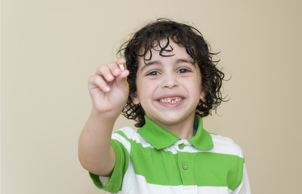 Child proudly holding his first lost baby tooth