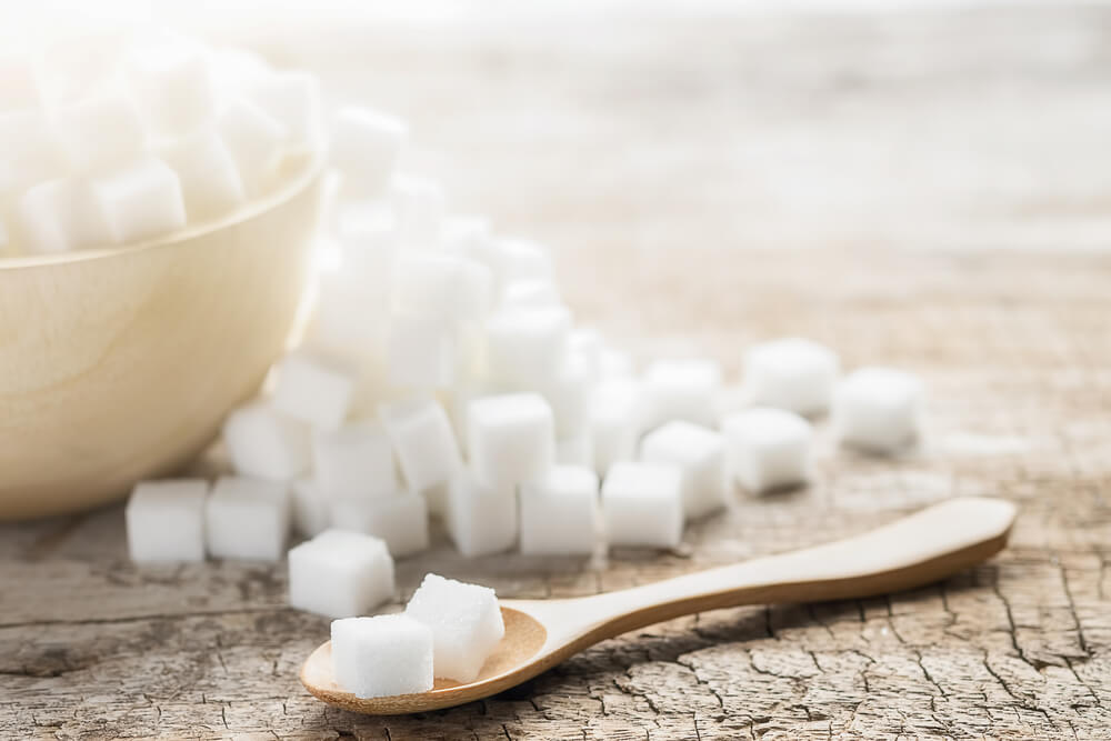 Bowl of sugar cubes with wooden spoon