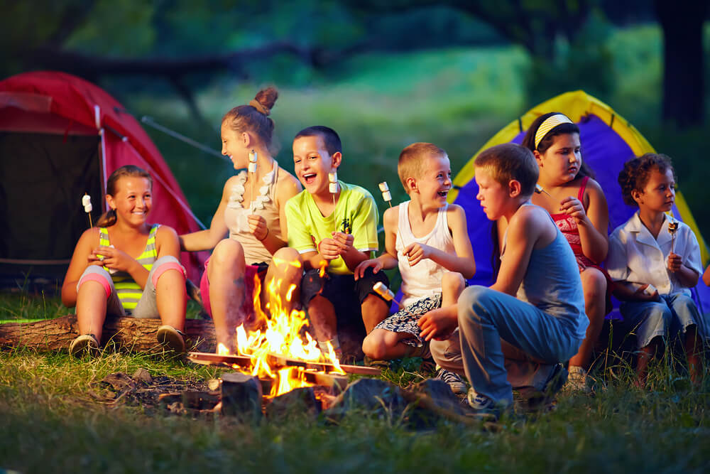 Children sitting around a campfire eating a s'mores