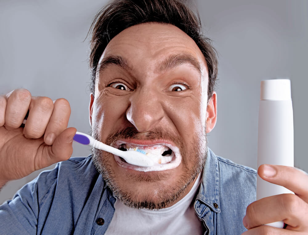 Man vigorously brushing his teeth.