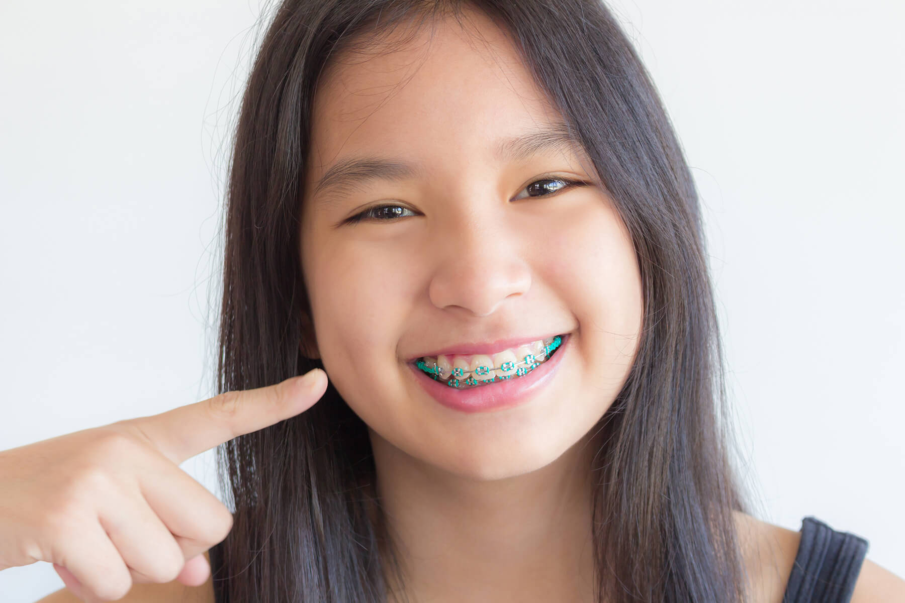 Girl smiling and pointing at her braces