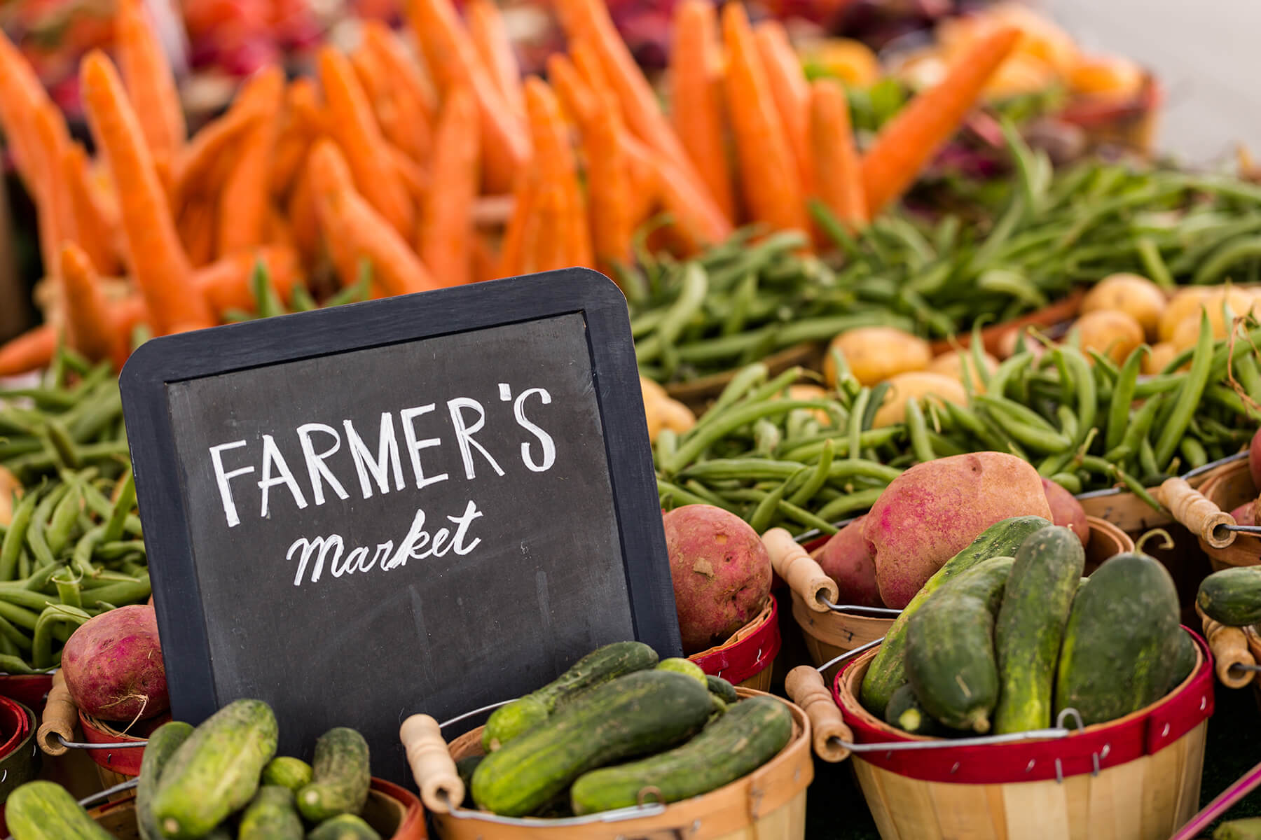 Farmers' Market sign in a group of veggies