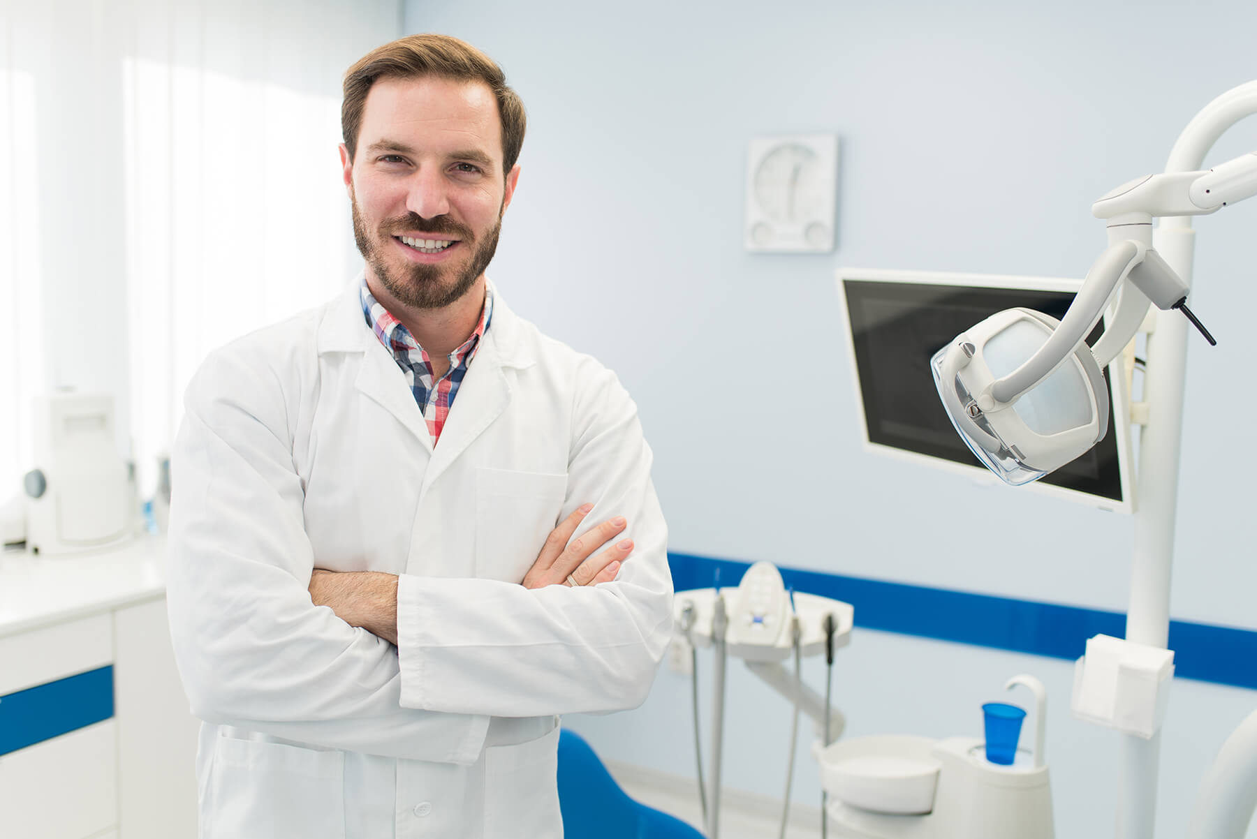 Male dentist standing in front of dental chair