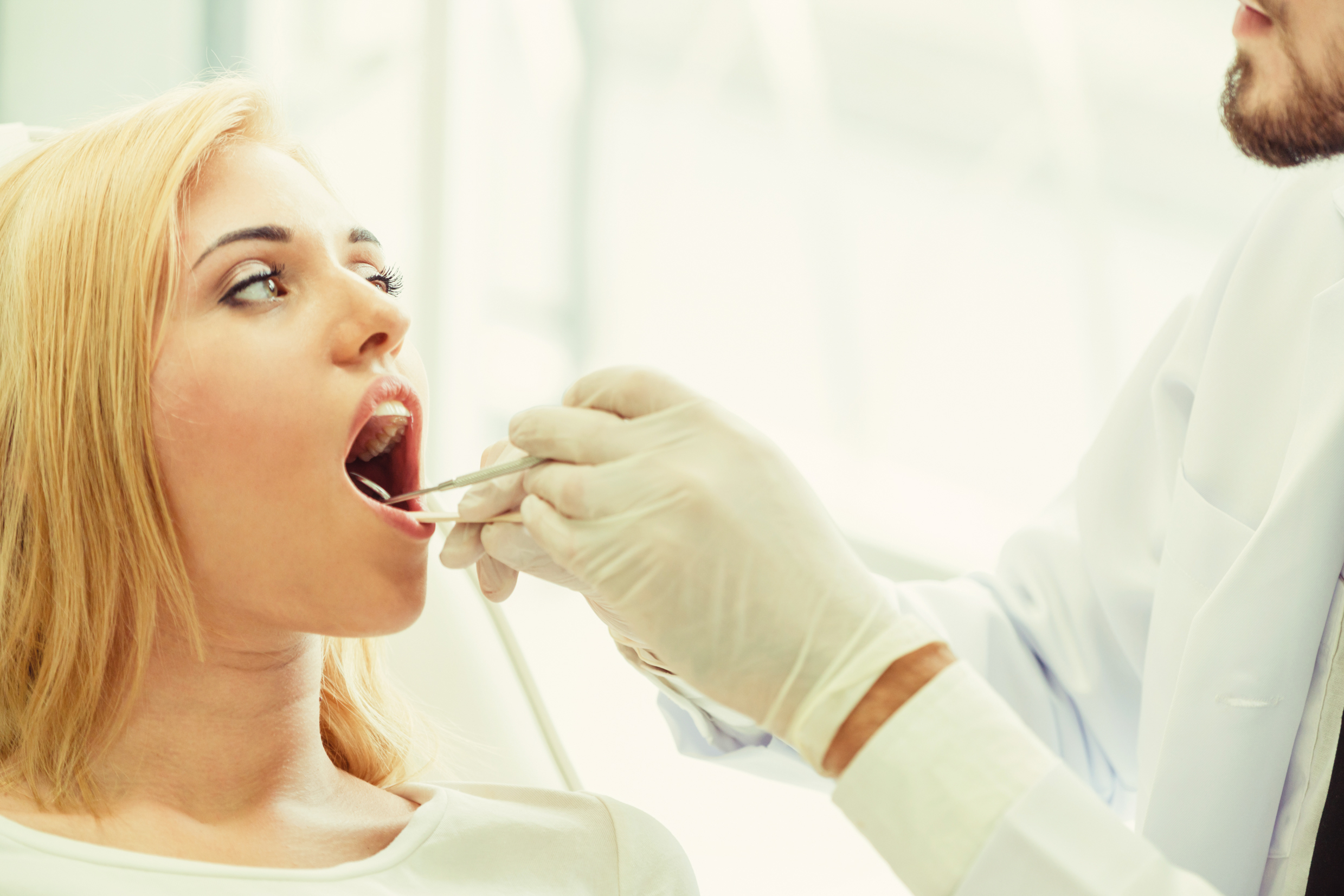 Dentist examining a patient's cheek for oral cancer