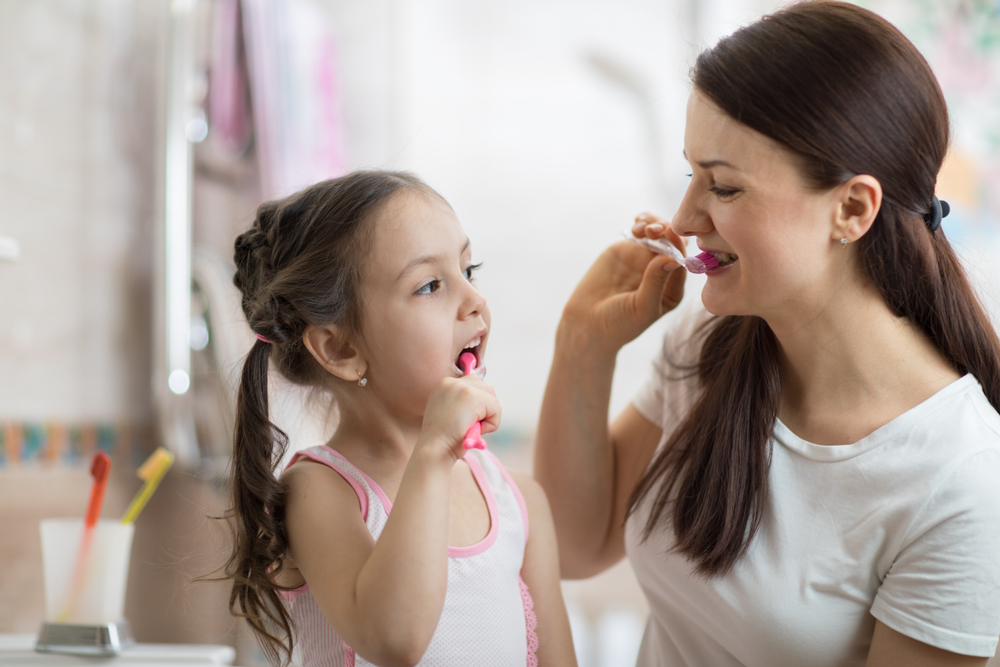 Mother teaching daughter to brush with fluoride toothpaste