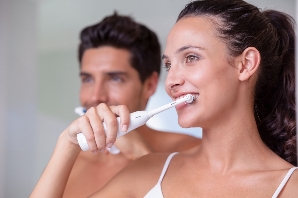 Woman and man using electric toothbrushes