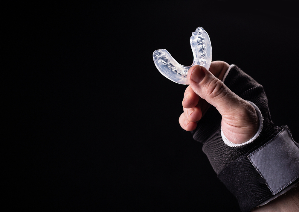 Man's hand holding a mouthguard